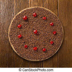 Sweet raw pizza with chocolate and cherry on wooden...