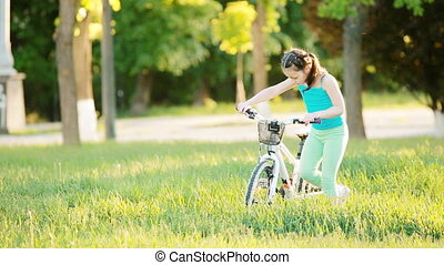 Happy child riding a bike in the city park at summer warm...