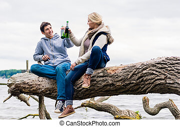 couple sitting on tree stump at the riverside drinking beer