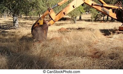 Backhoe out in the field - A backhoe digging up some dirt...
