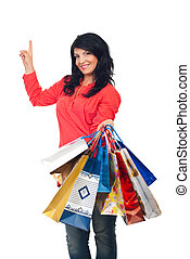 Woman with shopping bags pointing up - Beautiful happy woman...