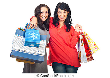 Happy women embracing at shopping - Happy women embracing...