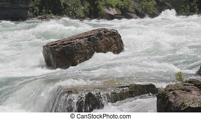 Rock in powerful river rapids - Rock stands against the...