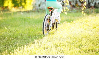 Happy little girl riding a bike in outdoor on green grass in the city park.