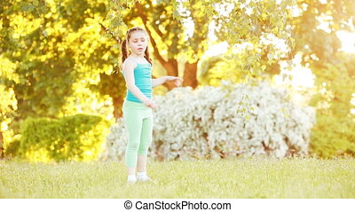 Cute little girl walking under tree in the park at sunshine summer day.
