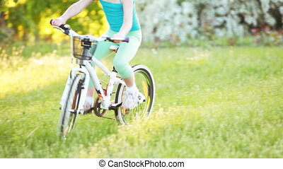 Happy little girl riding a bike in outdoor on green grass in...