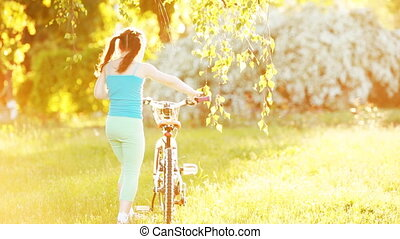 Happy little girl riding a bicycle on the meadow in summer sunshiny day.