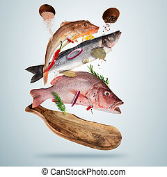 Fresh sea fish with falling spices, flying above wooden...