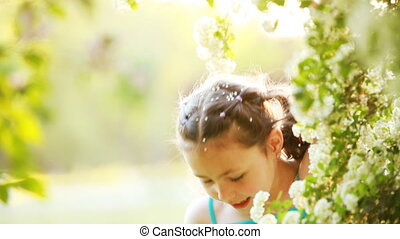 Close-up of little girl enjoys the smell of flowers in the...