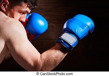 Portrait of young boxer fighter with boxing gloves against...