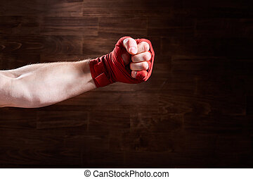 Boxer fist punch with red bandage on a wooden background.