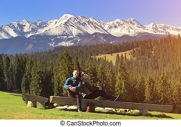Young couple on mountain background. Beautiful smiling...