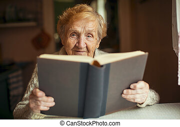 Russian elderly woman reading a book.