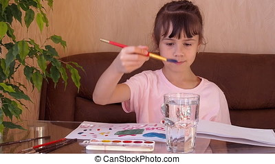 The girl paints with paint. The children draw houses on the table with paints. A brush is washed in a clear glass of water.