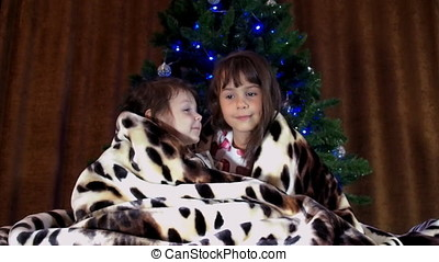 Children sit under a rug near the Christmas tree. Two little girls are covered with a spotted blanket. Two sisters play under a Christmas tree.