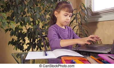 Little girl studying on a laptop