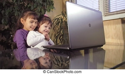 Family talking on Skype, two sisters on the laptop, at a...