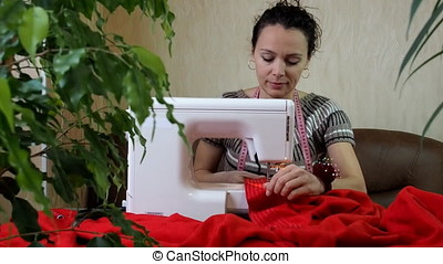 The work of the sewing machine. Woman tailor working on a...
