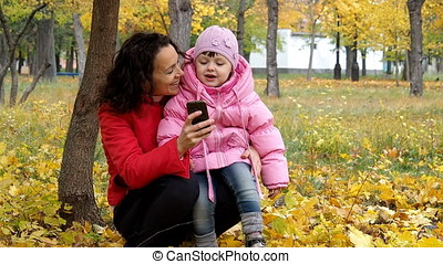 Mom and daughter are playing with the phone in the park