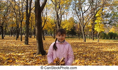 Girl in the park playing with autumn leaves.
