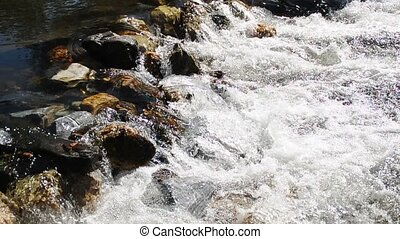 Small stream of water flowing over rocks - A small stream...