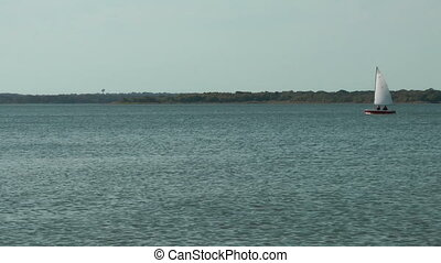 Sailboat moving across lake. - Sailboat moving across a...