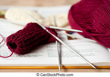 Knitted children sock with book and wool.