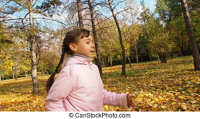 Happy child playing with autumn leaves