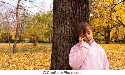 Kid talking on the phone in the park