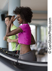 people exercisinng a cardio on treadmill in gym - young...