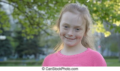 girl with freckles is smiling - Cute ginger girl with...
