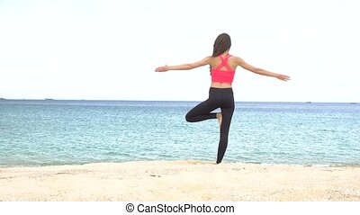The girl is making yoga pose on beach in Vietnam. Sea or ocean woman relaxation