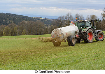Use fertilizer to fertilize - Farmers fertilize meadow with...