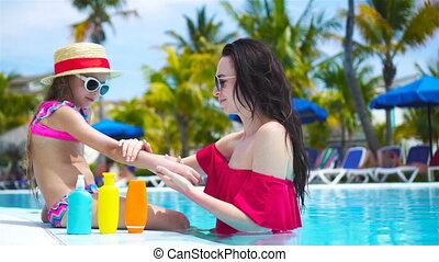 Young mother applying sun cream to kid hand outdoors. Sun...