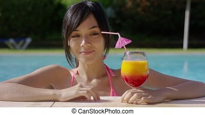 Woman eyeing a tropical cocktail with anticipation -...