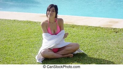 Smiling young woman wrapped in a white towel sitting on the...