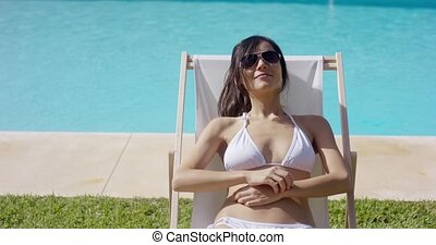 Smiling blissful young woman sunbathing
