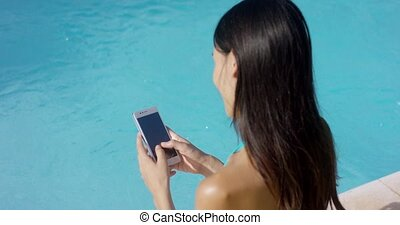 Young brunette woman checking her mobile