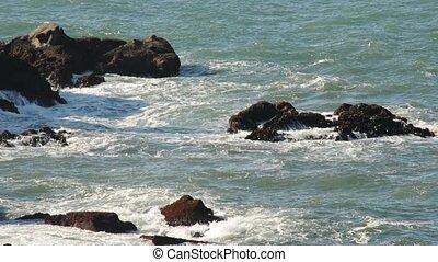 Waves Crash against ocean rocks