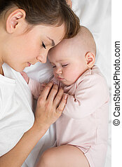 Mother with newborn baby sleeping on the bed at home. Top...