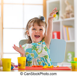 Smiling little girl is learning to use colorful play dough...