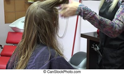 hair stylist make new haircut to blonde lady in salon. 4K -...