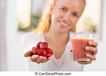 Girl holding strawberry and smoothie - Pretty blonde woman...