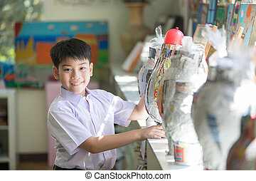 Happy asian child show his craft and looking camera