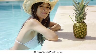 Pretty trendy young woman in a summer pool at a tropical...