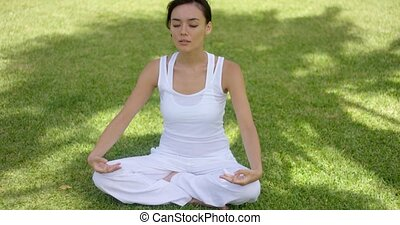 Pretty serene young woman meditating outdoors sitting in the...