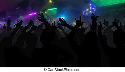 Silhouettes of concert crowd with hands raised at a music...