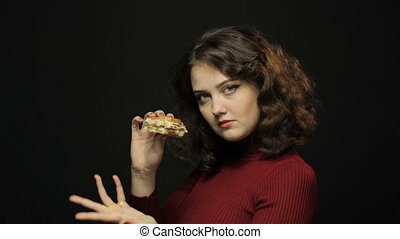 Beautiful woman eating fast food, closeup shooting on black...
