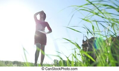 Girl wind nature. The girl is standing in the field of green grass. Woman lifestyle freedom