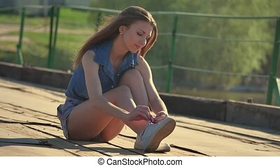 The girl tied her shoelaces. Girl sitting on a pontoon bridge iron old rusty
